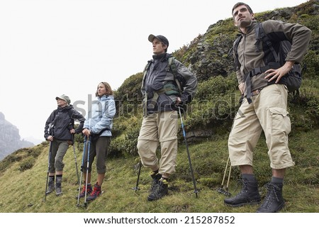 A group of people with backpacks walking along the road. There are mountains on the horizon. - stock photo