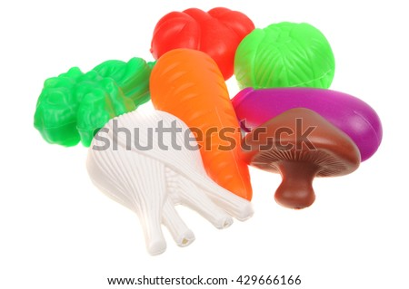 A group of plastic toy vegetables isolated on a white background - stock photo