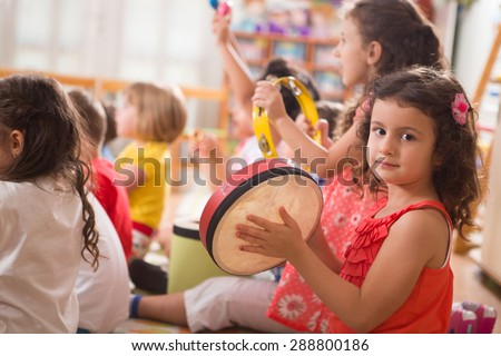 A group of preschool children in a music class.A little girl smiling at camera. - stock photo