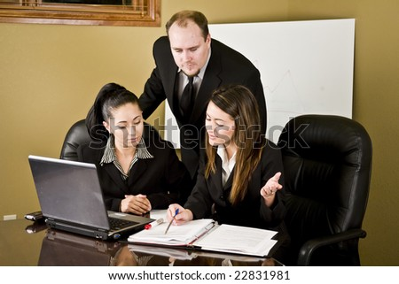 A group of professionals in a conference room going over information