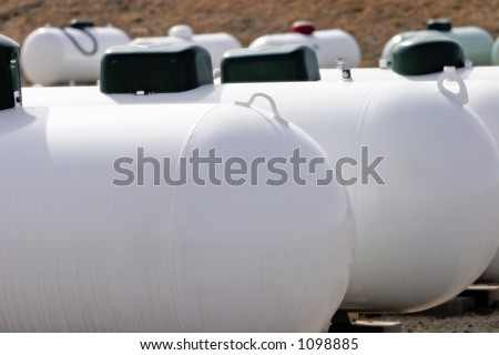 A group of Propane tanks at a Propane business located in rural America (focus point on foreground tank, shallow focus). - stock photo