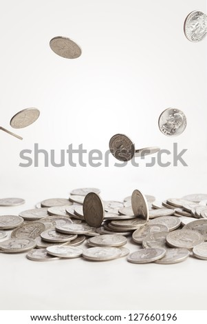A group of pure silver coins are falling down into a pile. - stock photo