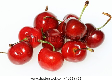 A group of ripe succulent fresh red cherries, with their stalks attached, on a white background.