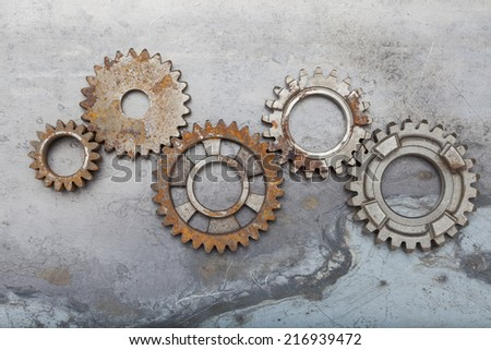 A group of rusty gears linked together on a steel background. - stock photo