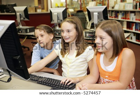 A group of school children having fun working on a computer in the school media center. - stock photo