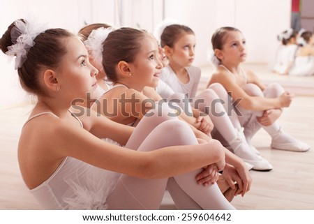 A group of six little ballerinas sitting on the floor gathered around their teacher and listen to advice. They are good friend and amazing dance performers - stock photo