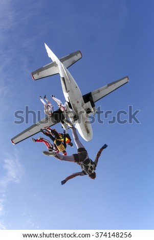 A group of skydivers jumping out of an airplane in free style.
