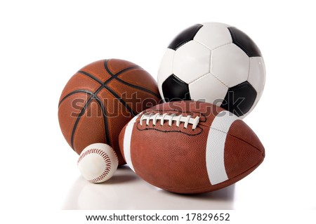 A group of sports balls on a white background, including a baseball, an American football, a basketball, and a soocer ball - stock photo