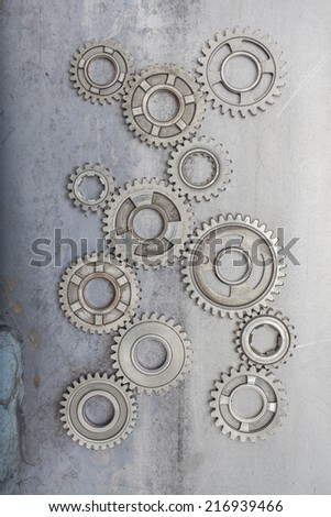 A group of steel gears linked together on a grungy metal background. - stock photo