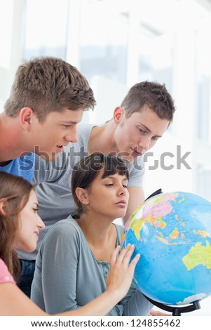 A group of students looking for a place in the world on a globe - stock photo