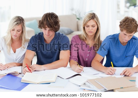 A group of students sitting at the table and studying