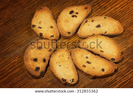 A group of sweet tasty rusks on wooden table - stock photo