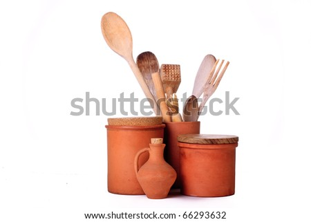 A group of terracotta kitchen containers with wooden utensils