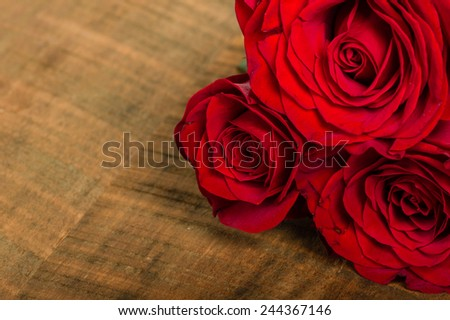 A group of three bright red roses on a wooden table - stock photo