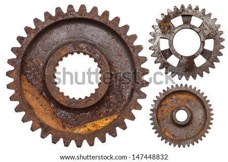 A group of three rusty transmission gears isolated on a white background. - stock photo
