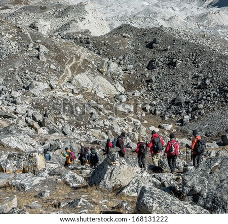 A group of tourists is on the moraine on the background of the massif Cho Oyu - Gokyo region, Nepal, Himalayas - stock photo