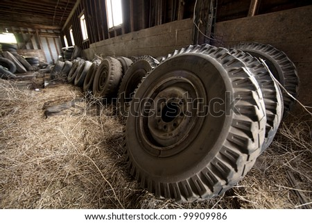 A group of tractor tires leaning against the barn wall.