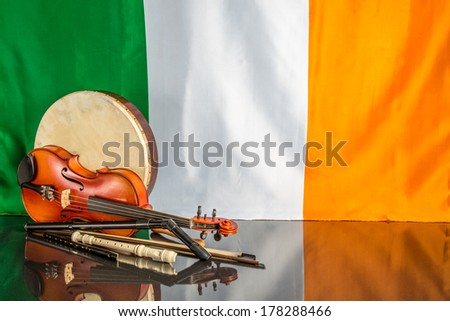 A group of traditional Irish musical instruments on a black table and Irish flag back ground - stock photo