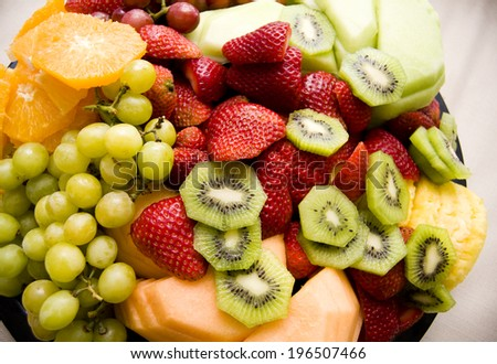 A group of various colorful fruits stacked on a tray. - stock photo