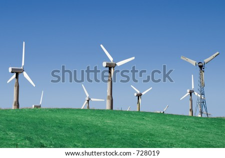 A group of windmills on rolling hills in California. - stock photo