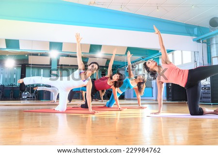 a group of women in sport dress at pilates and yoga exercise - stock photo