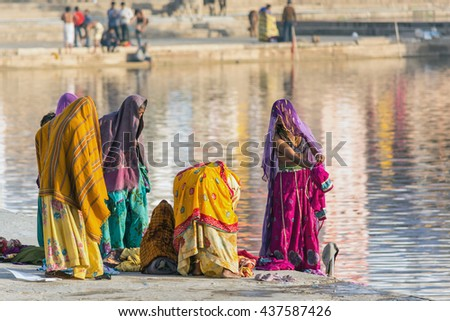 A group of women with colourful traditional garment performing ritual bath at holy lake in Pushkar, Rajastan, India