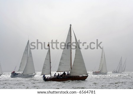 A group of yachts are racing in a Regatta. Yacht silhouettes fading out in a sunny fog - stock photo