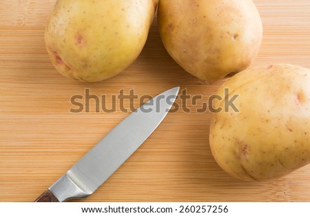 A group of yellow gold potatoes on a wood cutting board with a sharp knife. - stock photo