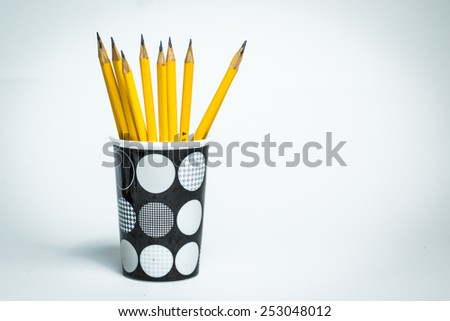 A group of yellow graphite pencils inside a cup on a white isolated background  - stock photo