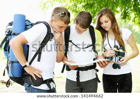 A group of young backpackers with map and binoculars - stock photo