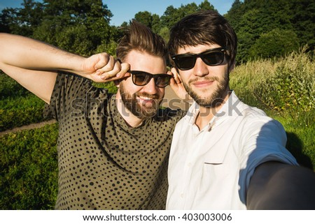 A group of young good looking multiethnic hipster friends do selfie photo portrait in the park while summer sunset - stock photo