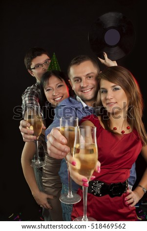 A group of young people dancing at night club and drinking champagne. New Year party.