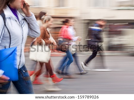 A group of young people going along the street. Intentional motion blur - stock photo