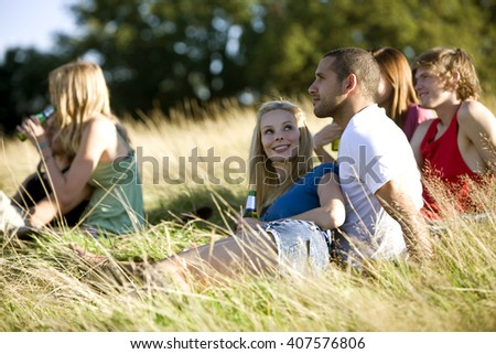 A group of young people sitting in a park, drinking beers - stock photo
