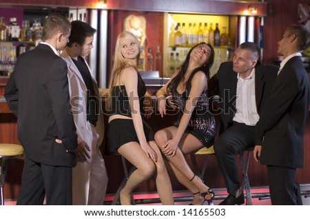 a group of young people sitting near the bar inside a night club - stock photo