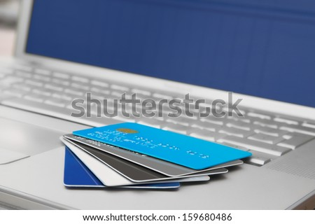 A Group off credit cards and bank cards on a Mobile Computer laptop keyboard - stock photo