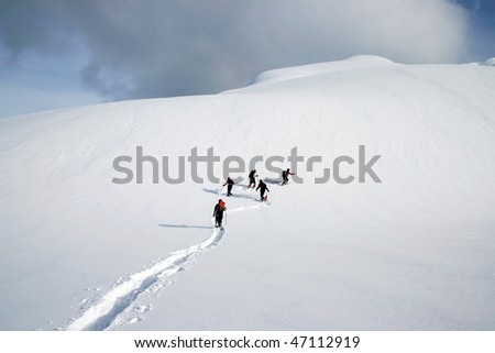 A group people are snowshoeing on the snow mountain in the winter season. In BC, Canada. - stock photo