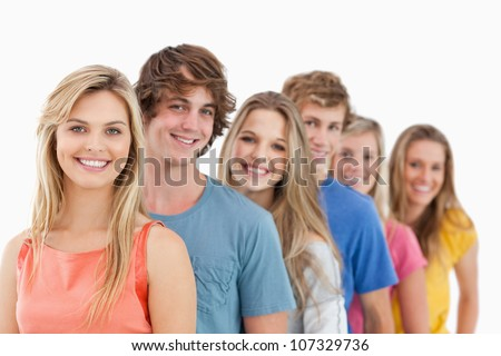 A group standing behind one another at an angle while looking at the camera - stock photo