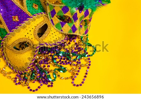 A group venetian, mardi gras mask or disguise on a yellow background with strings of beads - stock photo