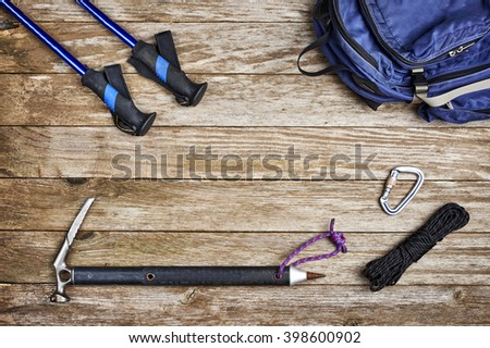 a grouping of camping gear including a backpack, trekking poles, rope and an ice axe - stock photo