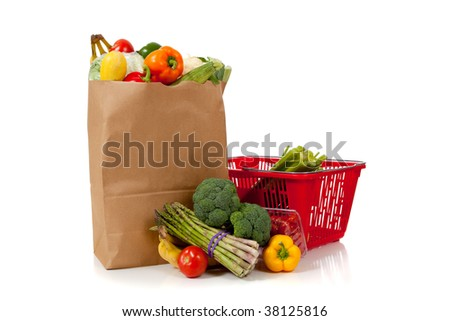 A grouping of fresh produce including fruits and vegetables in a grocery bag or sack with copy space - stock photo