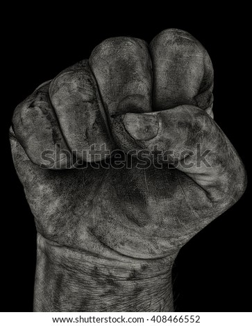 A grunge dirty monochrome aggressive clenched fist. Could be a coal miner. - stock photo