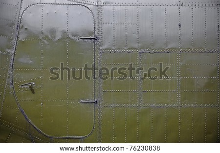 A grungy metal surface of an army airplane with an access door covered with rivets as textural background. - stock photo