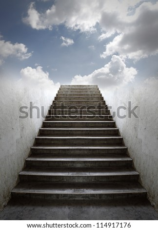 A grungy old concrete staircase going up into a blue cloudy sky. - stock photo