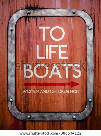 A Grungy Sign Pointing To Life Boats On An Old Ship