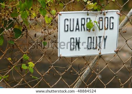 A guard dog on duty sign on a garden fence - stock photo