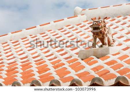 A guardian shisa lion dog, on the roof of an Okinawan home. - stock photo