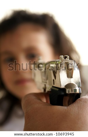 A gun aiming at a child's face - stock photo