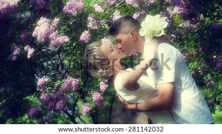 A guy and a girl, the couple kissing in blooming lilac - stock photo
