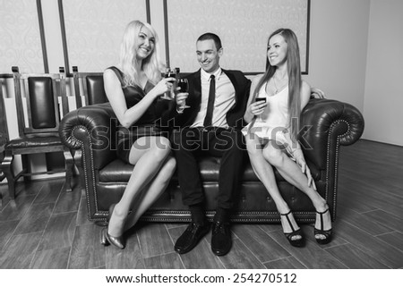 A guy and two girls in the room, tense. Group young people drink wine and enjoy the evening. Human feelings - jealousy, love, passion, betrayal.